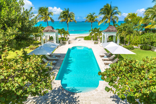 The luxury pool at Coral Pavilion Villa sits just a few yard from the beautiful Grace Bay Beach
