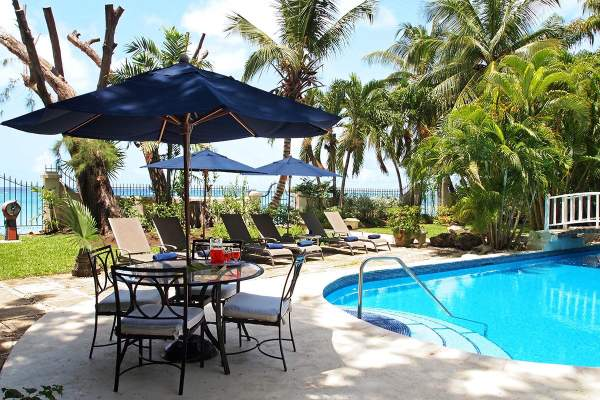 The pool at New Mansion is surrounded by tropical greenery and is just steps away from the ocean