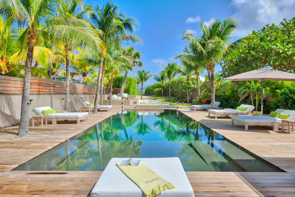 The luxurious pool and deck at Villa k and the path leading to the beach at Anse de Cayes