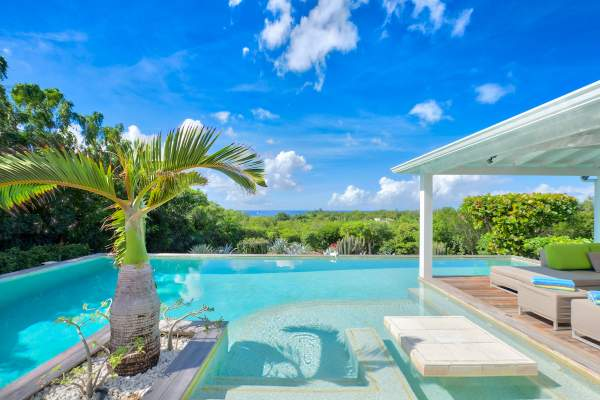 Lounge by the private pool while enjoying views of the Caribbean from the deck at Kiwi Villa